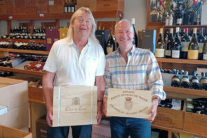 two men holding boxes of wine